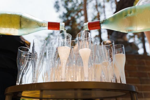 2 camerieri versano champagne in un bicchiere da vino di plastica usa e getta
