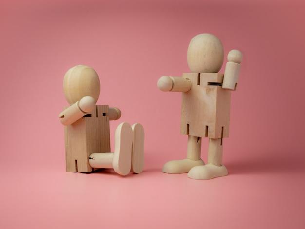 2 bambole di legno sedute e in piedi gesti di conversazione sullo sfondo rosa.