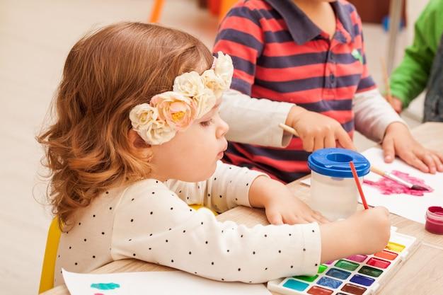 2 anni i bambini imparano a dipingere con un pennello e acquerelli su carta all'asilo