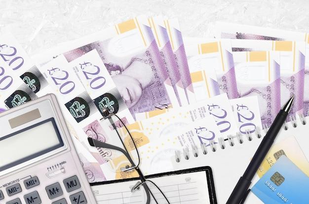 Bollette da 20 sterline inglesi e calcolatrice con occhiali e penna. concetto di stagione di pagamento delle tasse o soluzioni di investimento. pianificazione finanziaria o pratiche contabili