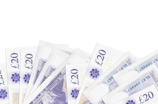 20 banconote in sterline britanniche si trovano sul lato inferiore dello schermo isolato sul muro bianco con spazio di copia.