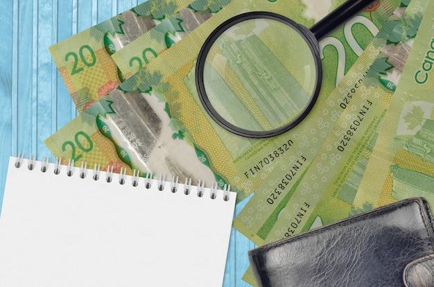 Banconote da 20 dollari canadesi e lente d'ingrandimento con borsa nera e blocco note