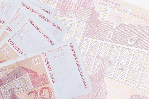 20 banconote in kune croate si trovano in una pila sul muro di una grande banconota semitrasparente. parete astratta di affari con lo spazio della copia
