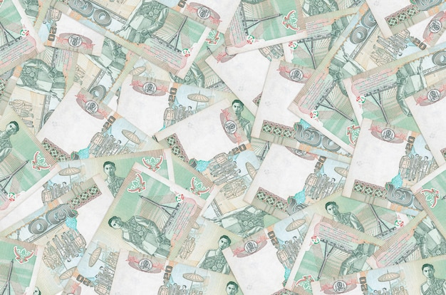 20 banconote in baht thailandesi si trovano in un grande mucchio. parete concettuale di vita ricca. grande quantità di denaro