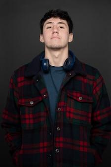Caucasico di 20 anni con le cuffie al collo e un piccolo sorriso su sfondo grigio