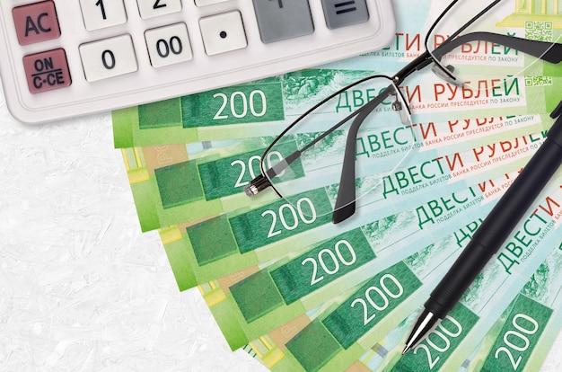 Ventilatore e calcolatrice da 200 rubli russi con occhiali e penna. prestito aziendale o concetto di stagione di pagamento delle tasse. progetto finanziario