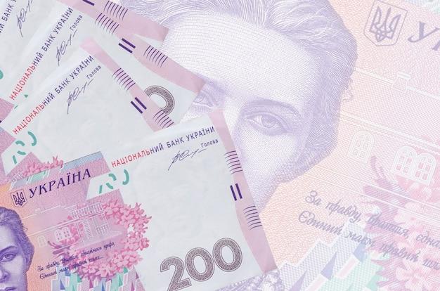200 banconote hryvnias ucraine si trovano in pila su sfondo di grandi banconote semitrasparenti