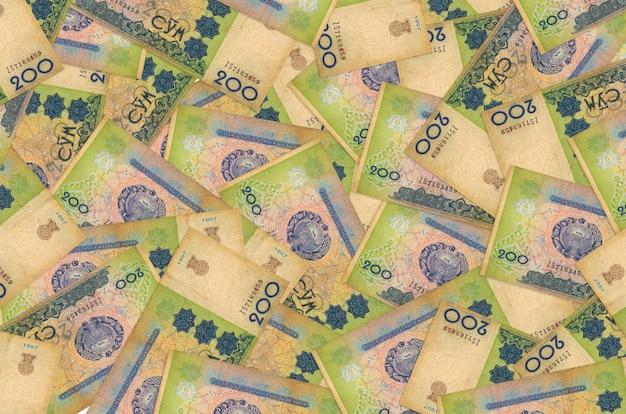 200 banconote som uzbeke si trovano in una grande pila. sfondo concettuale di vita ricca. grande quantità di denaro