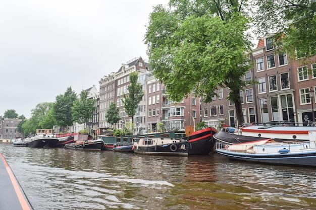 2016: vista del livello dell'acqua da uno dei canali di uno degli edifici storici e delle barche di amsterdam, paesi bassi