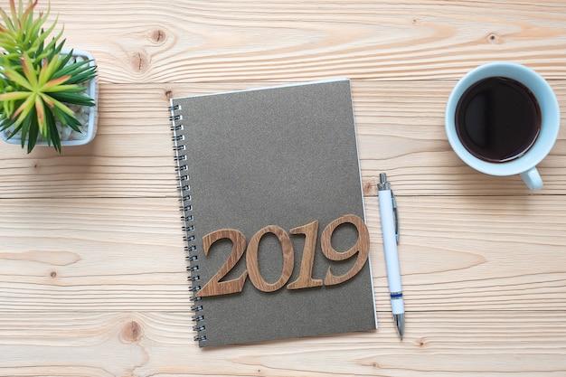 2019 happy new year con notebook, tazza di caffè nero, penna e bicchieri