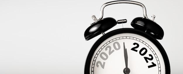 2020 e 2021 sulla sveglia nera con copia spazio, buon natale e felice anno nuovo concetto.