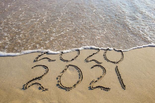 2020, 2021 anni scritti sulla spiaggia sabbiosa del mare