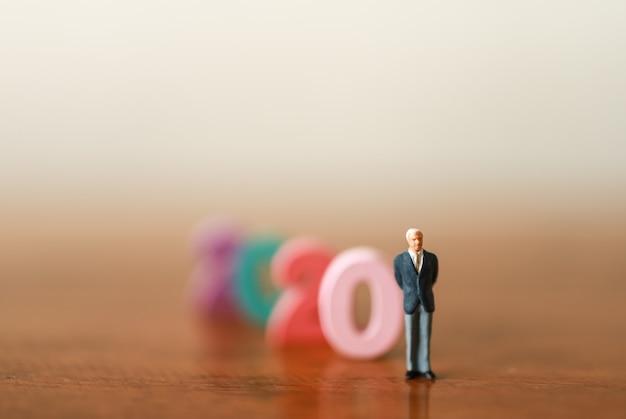2020 concetto di business. primo piano della figura in miniatura dell'uomo d'affari persone in piedi con il numero di legno colorato sul tavolo wooen e lo spazio della copia.