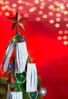 Albero di natale 2020 decorato con ornamenti di luci colorate e mascherine chirurgiche con una stella rossa sulla punta e uno sfondo rosso con bokeh di stelle