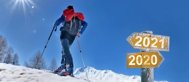 2021 e 2020 scritti su un cartello con un uomo in alpinismo sci alpinismo Foto Premium