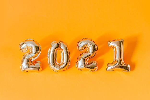 2021 numeri di palloncini in lamina d'oro aria con spazio di copia su sfondo arancione.