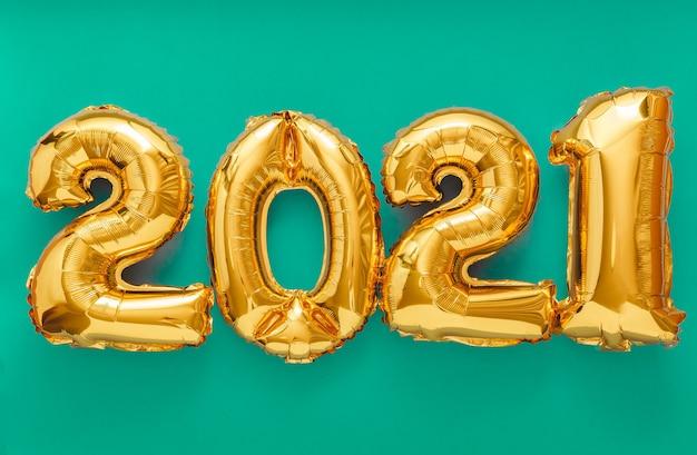 Testo del fumetto 2021 su verde. felice anno nuovo invito vigilia con palloncini natalizi in lamina d'oro 2021.