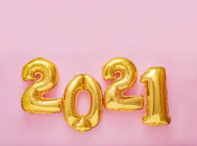 Testo del fumetto 2021 sul rosa. felice anno nuovo invito vigilia con palloncini natalizi in lamina d'oro 2021