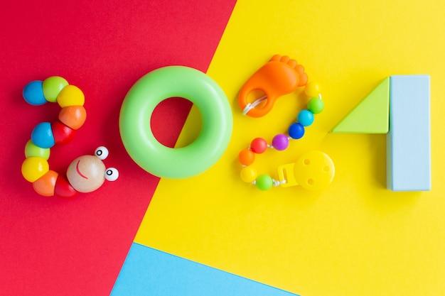Bambini di natale 2021. numeri da blocchi di costruzione arcobaleno e giocattoli su uno sfondo colorato luminoso. giocattoli educativi colorati per bambini. le parole. vista dall'alto. lay piatto.