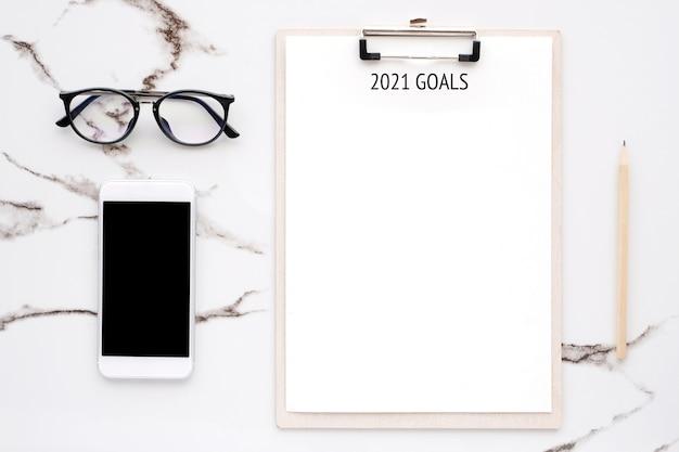 Obiettivi 2021 su carta per appunti in bianco con copia spazio per testo e smartphone