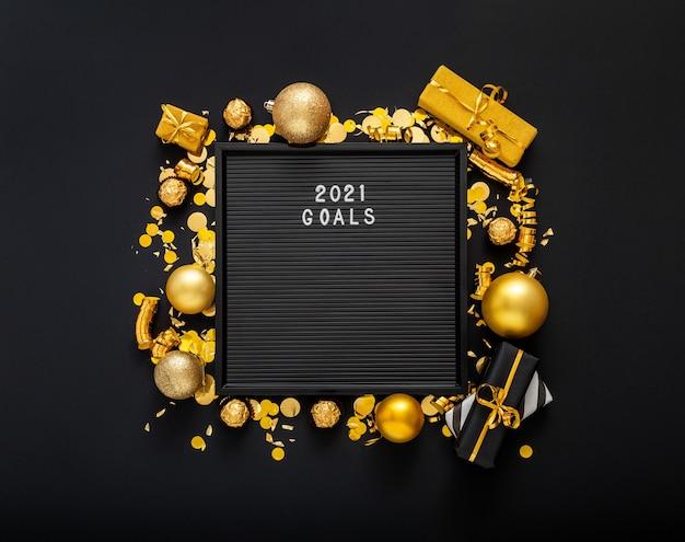 Testo degli obiettivi 2021 su lavagna nera con cornice in decorazioni natalizie dorate.