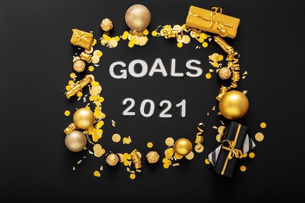 Iscrizione di testo obiettivi 2021 su superficie nera in cornice in decorazioni natalizie dorate