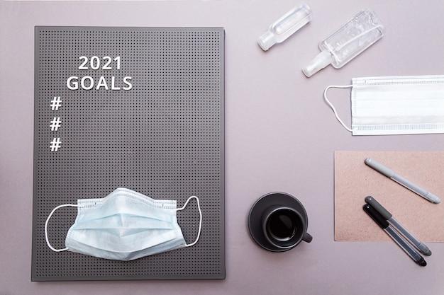 Obiettivi 2021 con maschera protettiva per il viso, flaconi igienizzante mani e tazzina da caffè