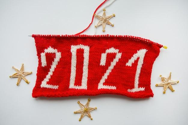Felice anno nuovo 2021. numero lavorato a maglia. e fiocchi di neve di paglia su sfondo bianco. foto di alta qualità