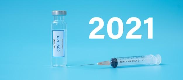 2021 felice anno nuovo con la fiala di vaccino covid-19 e la siringa con ago per iniezione