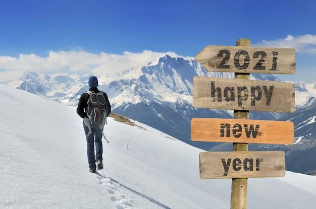 Felice anno nuovo 2021 scritto su un cartello con un escursionista che cammina sulla neve in una montagna