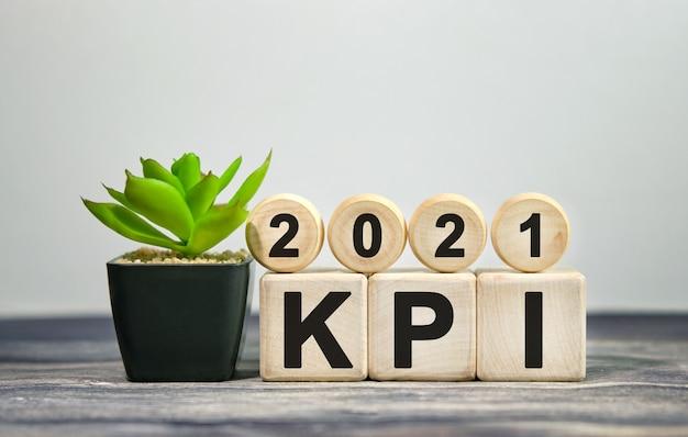 Kpi 2021 - concetto finanziario. cubetti di legno e fiore in vaso.