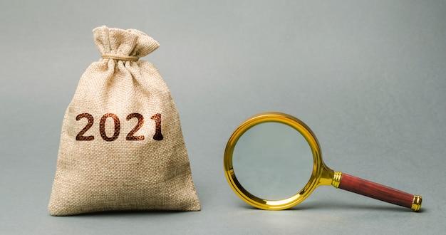 Sacco di soldi 2021 e lente d'ingrandimento pianificazione del budget obiettivi e piani finanziari