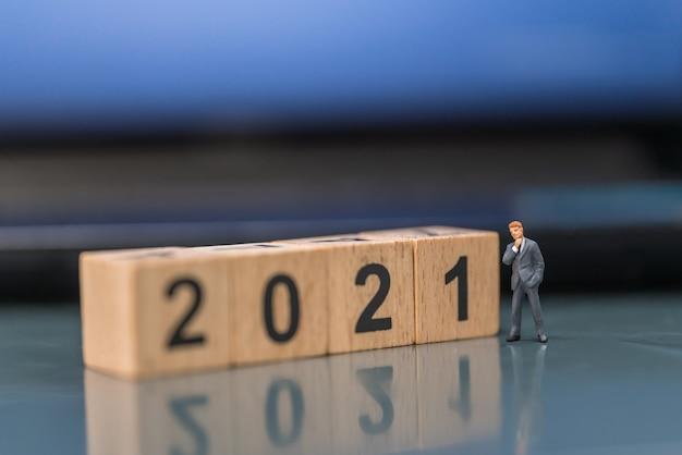 Anno nuovo 2021, concetto di affari. persone di figura in miniatura dell'uomo d'affari in piedi con il blocco numerico in legno.