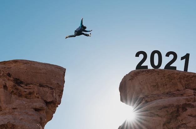 Concetto del nuovo anno 2021, silhouette di un uomo che salta al 2021