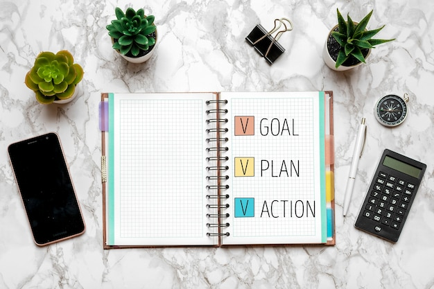 Obiettivo del nuovo anno 2021, piano, testo d'azione sul blocco note aperto, occhiali, tazza di caffè, penna, smartphone