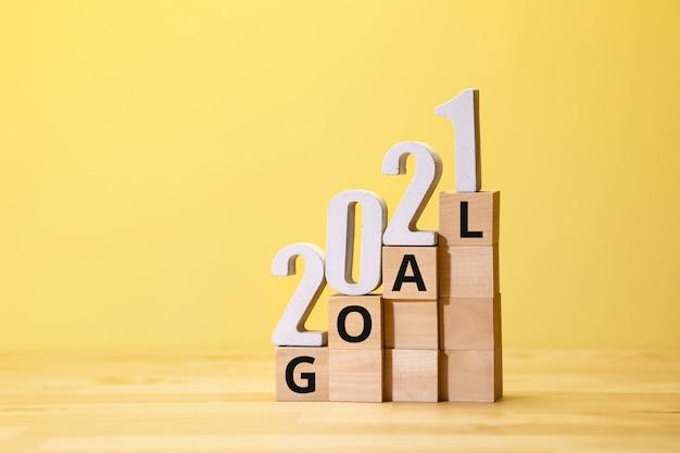 Obiettivo del nuovo anno 2021 sul passo della scatola di legno sul colore giallo risoluzione aziendale e concetti di piano