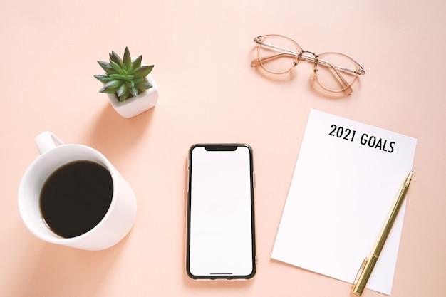 Concetto di risoluzioni del nuovo anno 2021 sulla foto piatta della scrivania dell'area di lavoro con smartphone, caffè, nota di carta con sfondo spazio copia, stile minimal