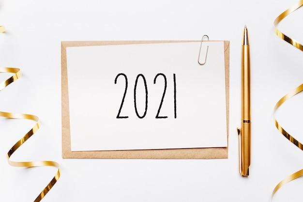 Nota 2021 con busta, penna, regali e nastro d'oro su sfondo bianco. buon natale e anno nuovo concetto