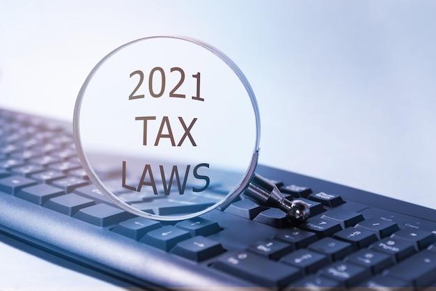 Testo delle leggi fiscali 2021 su una lente d'ingrandimento, che si trova sulla tastiera. concetto aziendale e fiscale