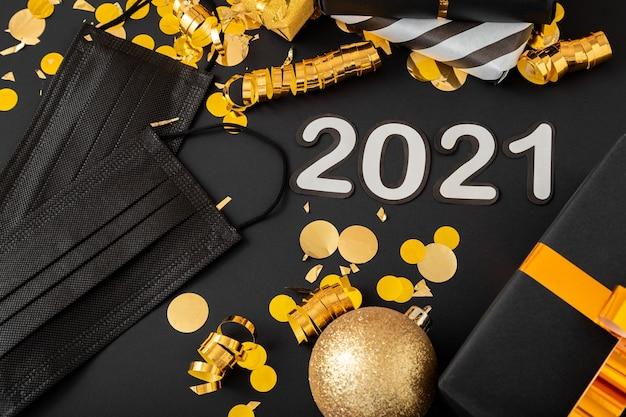 Iscrizione di testo 2021 con maschere mediche nere, decorazioni festive in oro. anno nuovo covid 19.