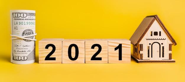 2021 con modello in miniatura di casa e denaro su sfondo giallo. il concetto di business, finanza