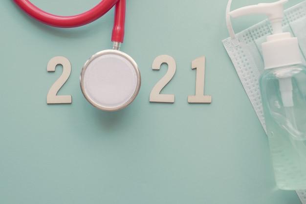Numero 2021 in legno con stetoscopio rosso, maschera facciale e disinfettante per le mani.