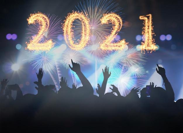 2021 scritto con fuochi d'artificio sparkle sulla folla di concerti in sagome di fanclub musicale con azione di spettacolo per festeggiare con fuochi d'artificio, felice anno nuovo