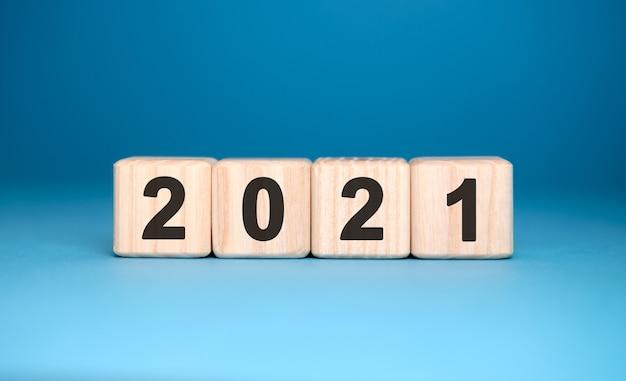 2021 anni su cubi di legno su uno sfondo blu sfumato