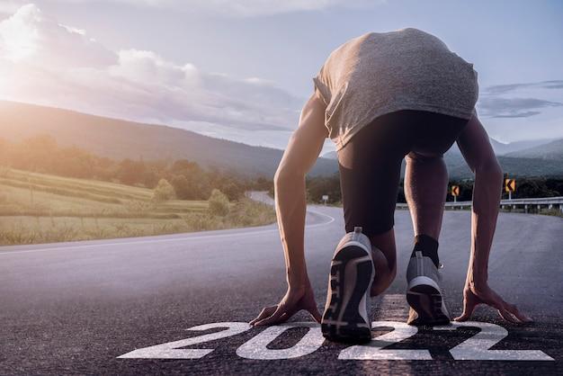 Sfondo 2022. piedi del corridore che corrono sul primo piano della strada sulla scarpa. concetto a partire dal 2022.