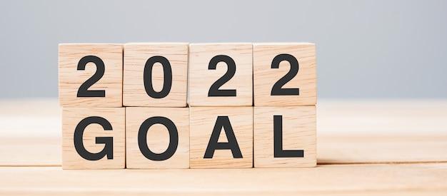 2022 obiettivo cubo blocco sullo sfondo della tabella. risoluzione, pianificazione, revisione, modifica, inizio e concetti di vacanza di capodanno