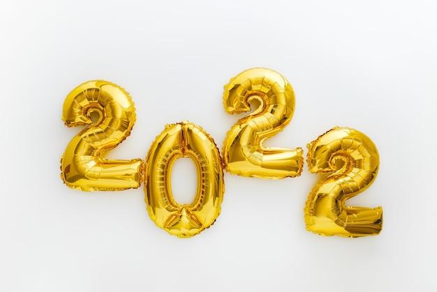 Testo di palloncini d'oro 2022 invito alla vigilia di capodanno con calendario di palloncini di lamina d'oro di natale. palloncino numerale 2022 su sfondo bianco per la celebrazione di natale e capodanno. banner web lungo.