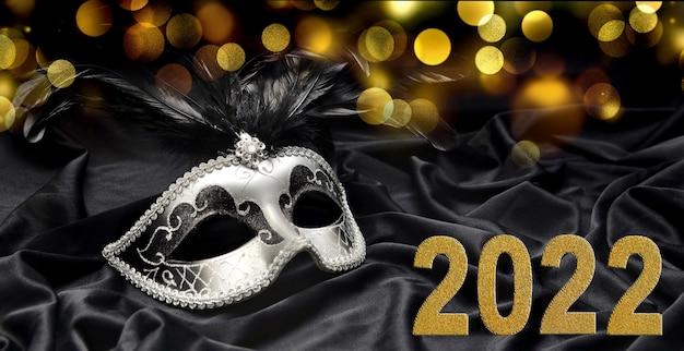 Biglietto di auguri 2022 con maschera di carnevale veneziano su tessuto scuro e sfondo di luci sfocate
