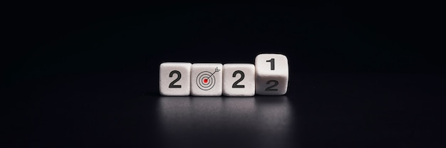 Banner di felice anno nuovo 2022 con obiettivo aziendale e concetto di successo. lancio di blocchi di dadi neri per cambiare i numeri dal 2021 al nuovo anno 2022 su sfondo scuro, stile moderno e minimale.