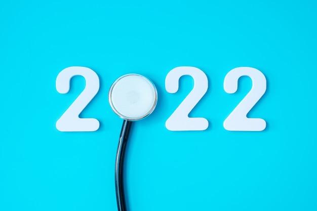 2022 felice anno nuovo per l'assistenza sanitaria, le assicurazioni, il benessere e il concetto medico. stetoscopio e numero bianco su sfondo blu